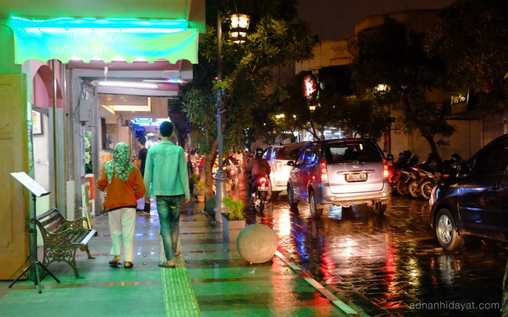 Dua orang disinari cahaya lampu hijau dari toko